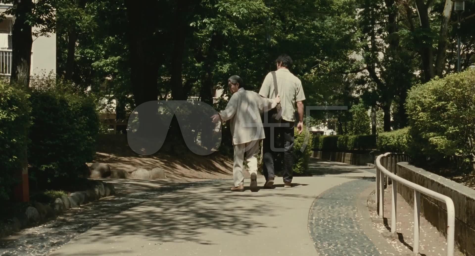 年迈的母亲和儿子在路上的背影