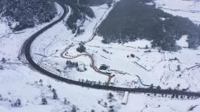 4k航拍,冬天白雪覆盖的田野和有车辆行驶视频素材包