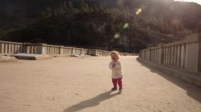 在公園的一座橋上,一名女嬰正在學習走路。視頻素材
